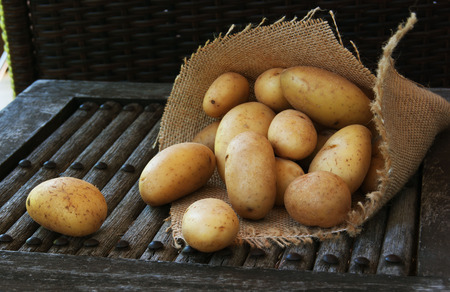fruits of potatoes on a wooden surface in the bag
