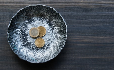 restaurant bill: small textured metal plate with euro coins on a wooden black background Stock Photo