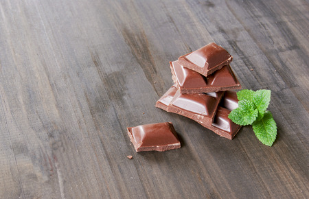 endorphine: pieces of chocolate with mint lying on a wooden surface