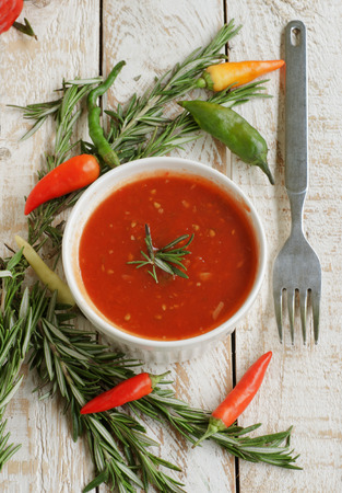 pureed: bowl of tomato hot sauce with peppers, rosemary and cutlery