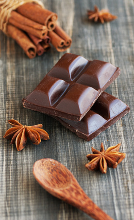endorphine: pieces of chocolate with cinnamon, anise and candied lying on a wooden surface