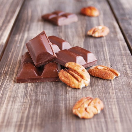 endorphine: pieces of chocolate with walnuts lying on a wooden surface Stock Photo