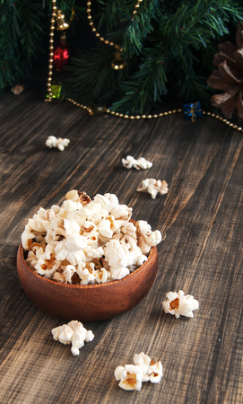 eating popcorn: popcorn in a wooden plate on the background of Christmas trees and Christmas decorations, New Year offer, selective focus