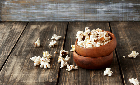 popcorn bowls: popcorn in a wooden bowl on a wooden background, selective focus