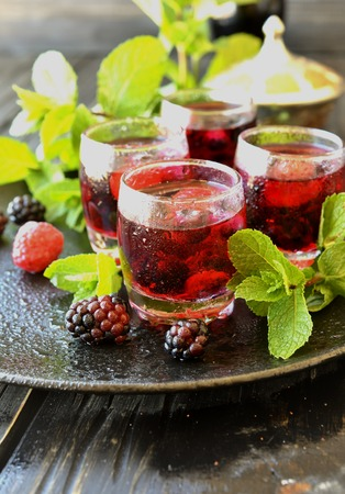selective focus: berry juice in a glass with berries, ice and mint, selective focus