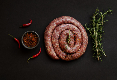 raw beef sausages on a cast-iron pan with rosemary and spices on a wooden table, South African boerewors