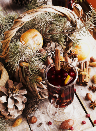 vin chaud: A cup of hot wine with spices and nuts Christmas card with fir-tree branches