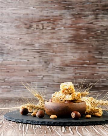barra de cereal: Barra de cereales con almendras y nueces sobre la mesa de madera, enfoque selectivo Foto de archivo