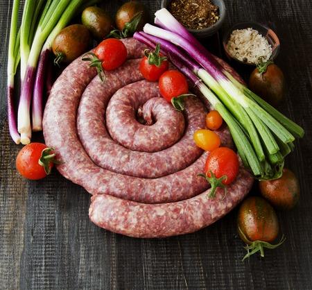 carne roja: embutidos de carne sin procesar con romero y especias en una mesa de madera, boerewors sudafricanas Foto de archivo