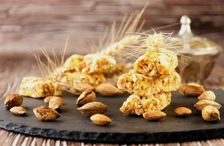 barra de cereal: Barra de cereal con frutos secos y miel, enfoque selectivo