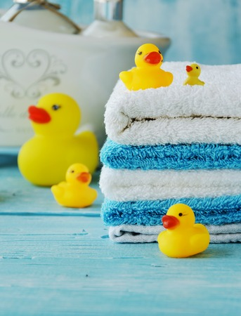 bathroom duck: stack of colorful towels and bath duck on the table, accessories for the bathroom Stock Photo