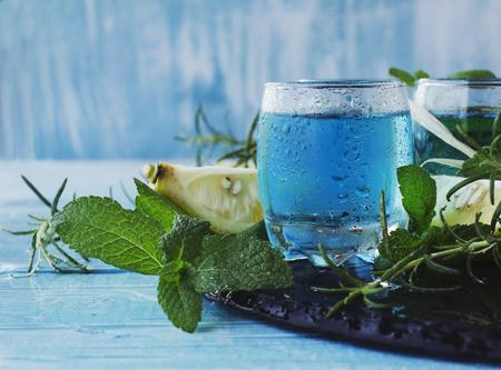 Blue curacao liqueur or sambuca with lemon on the wooden table, selective focus