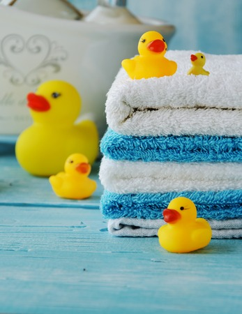 stack of colorful towels and bath duck on the table, accessories for the bathroom Stock Photo