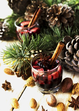 New Year or Christmas composition with walnuts, mulled wine, hazelnuts, pistachios in canvas bags with fir branches and cones. wood background, selective focus