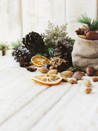 New Year or Christmas composition with walnuts, mulled wine, hazelnuts, pistachios in canvas bags with fir branches and cones. wood background, selective focus Stock Photo