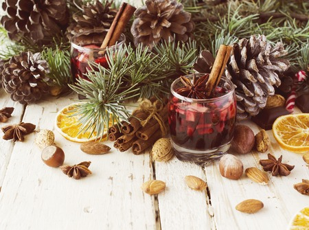 nutshells: New Year or Christmas composition with walnuts, mulled wine, hazelnuts, pistachios in canvas bags with fir branches and cones. wood background, selective focus Stock Photo