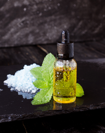 menthol: jar of menthol oil, a sprig of mint and salt on black stone table for spa, selective focus, space for text Stock Photo