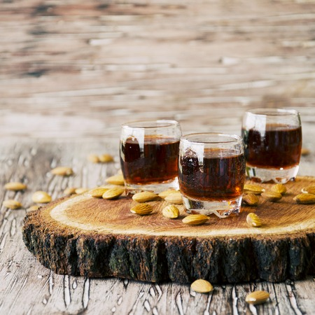 snifter: Italian liqueur Amaretto in cups with almonds on a wooden table, selective focus