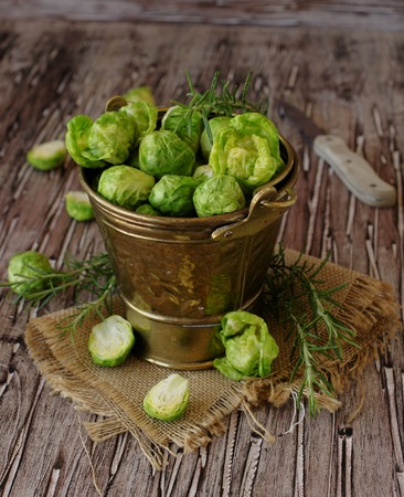 green raw brussels sprouts in the copper old bucket with rosemary on rustic wooden table, selective focus Stock Photo
