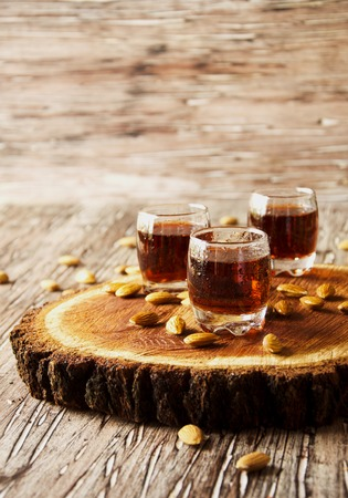 amaretto: Italian liqueur Amaretto in cups with almonds on a wooden table, selective focus