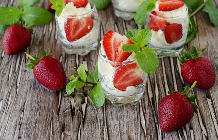 wimbledon: Strawberries with cream or tiramisu in small glasses with mint, vintage wooden background, selective focus