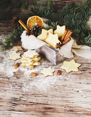 jewish star: Christmas or new year gingerbread cookies in a Jewish star in a wooden box with cinnamon, almonds, dried slices apelchina and spruce twigs on rustic table, selective focus Stock Photo