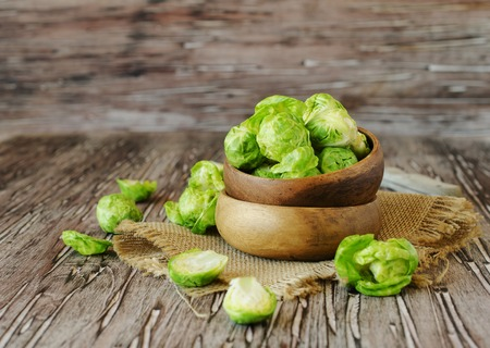 Green raw Brussels sprouts in wooden bowl , selective focus