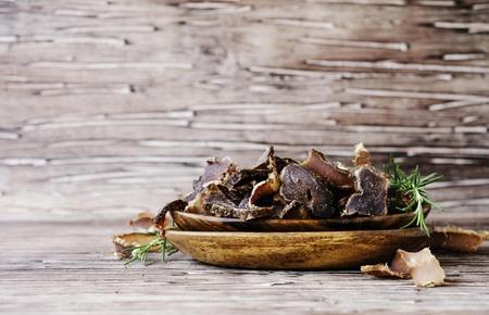 얼룩 덜 룩 한 고기, 소, 사슴, 야생 짐승 또는 biltong 나무 그릇에 소박한 테이블, 선택적 포커스