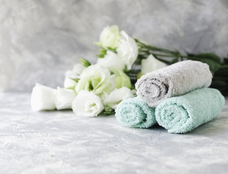 stack of towels marble table set with flowers for spa space under the text, selective focus