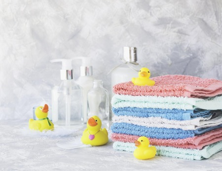 stack of towels with yellow rubber bath ducks and means for bathroom on white marble background, space for text, selective focus