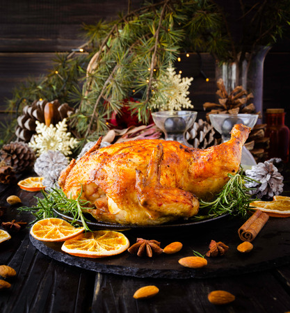 Roast chicken or turkey for Christmas and New Year with mulled wine and Christmas decorations, selective focus