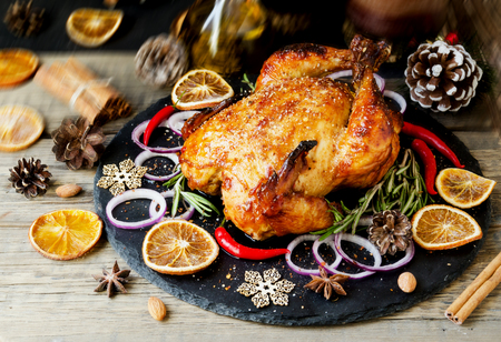 Roast chicken or turkey for Christmas and New Year with mulled wine and Christmas decorations, space for text, selective focus Stock Photo