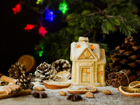 Christmas card with little toy house and Christmas decorations on a wooden rustic table, selective focus Stock Photo