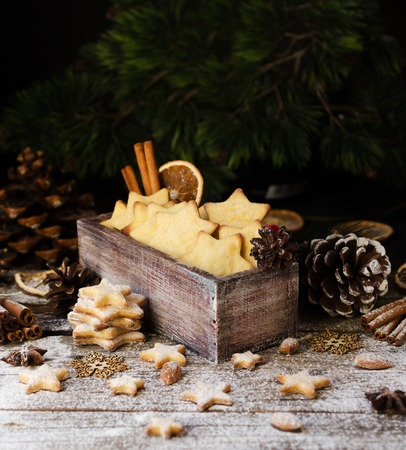 Christmas or new year gingerbread cookies in a Jewish star in a wooden box with cinnamon, almonds, dried slices apelchina and spruce twigs on rustic table, selective focus Stock Photo