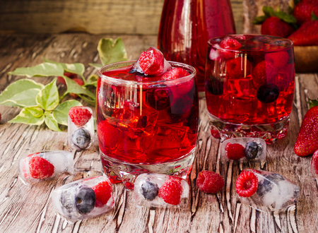 Summer berry lemonade with frozen berries and a jug on a wooden rustic table, selective focus Stock Photo
