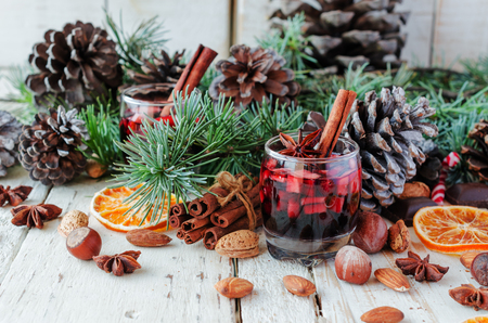 A glass of hot mulled wine for the new year with ingredients for cooking, nuts and Christmas decorations, a Christmas card, selective focus, space for text, a low key