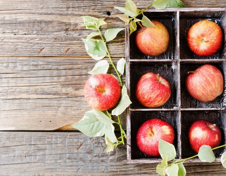 ripe red apples in a wooden box on a rustic table, selective focus