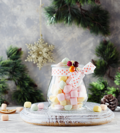 a small glass jar with marshmallows for Christmas and New Year on a wooden white table, selective focus