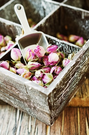 small dry buds of roses, tea, karkade, in wooden box, selective focus