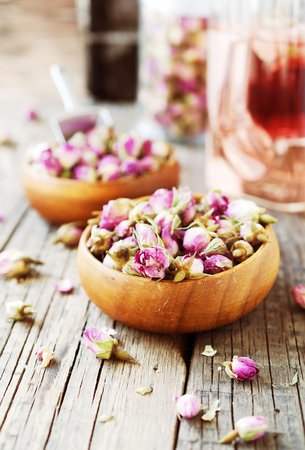 small dry buds of roses, tea, karkade, in wooden bowls, selective focus
