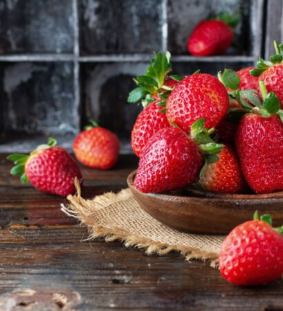 red ripe strawberry in a wooden bowl on a rustic table, close-up, selective focus Stock Photo