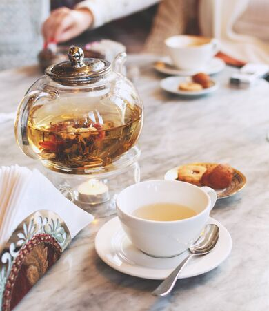 Transparent glass teapot with green tea on a marble table in a cafe, with a cup, selective focus