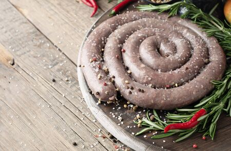 raw beef sausages with rosemary and spices on a wooden table, South African boerewors