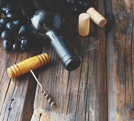 Bottle of red wine with fresh grape and bunch of corks on wooden table, background selective focus - Image Stock Photo