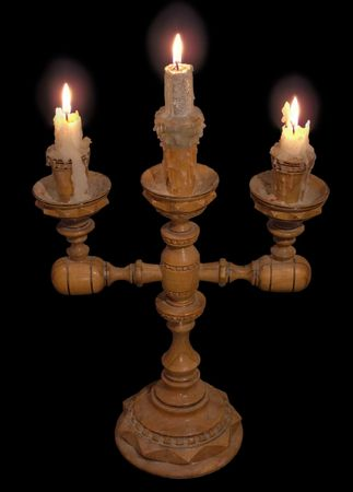 Wood candlestick with 3 shine candles (isolated on black)