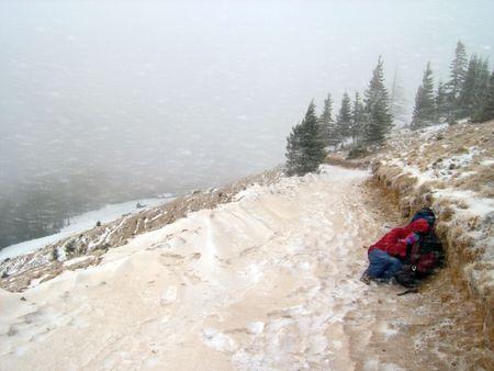 sgomento: inverno neve e polvere tempesta con costernazione figura umana in montagna su strada e per vivere l'agricoltura di montagna soluzione dietro Archivio Fotografico