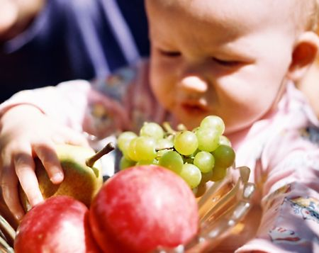 kind met fruit in de zomer bloeiende tuin nabij moeder (softfocus) Stockfoto