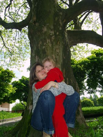 Mother and  daughter under big tree in park photo