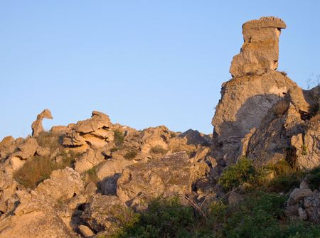 Quaint stone shapes (lake serpent and big man) on rocky terrace (
