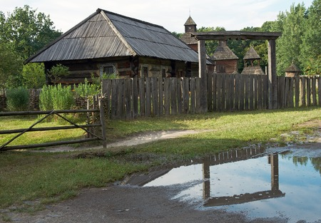 country wood farmstead and arc repulse in puddle (with church behind, stump beehive in courtyard), (preceding century, museum of Ukrainian folk architecture in Pirogovo village (near Kiev)) Stok Fotoğraf